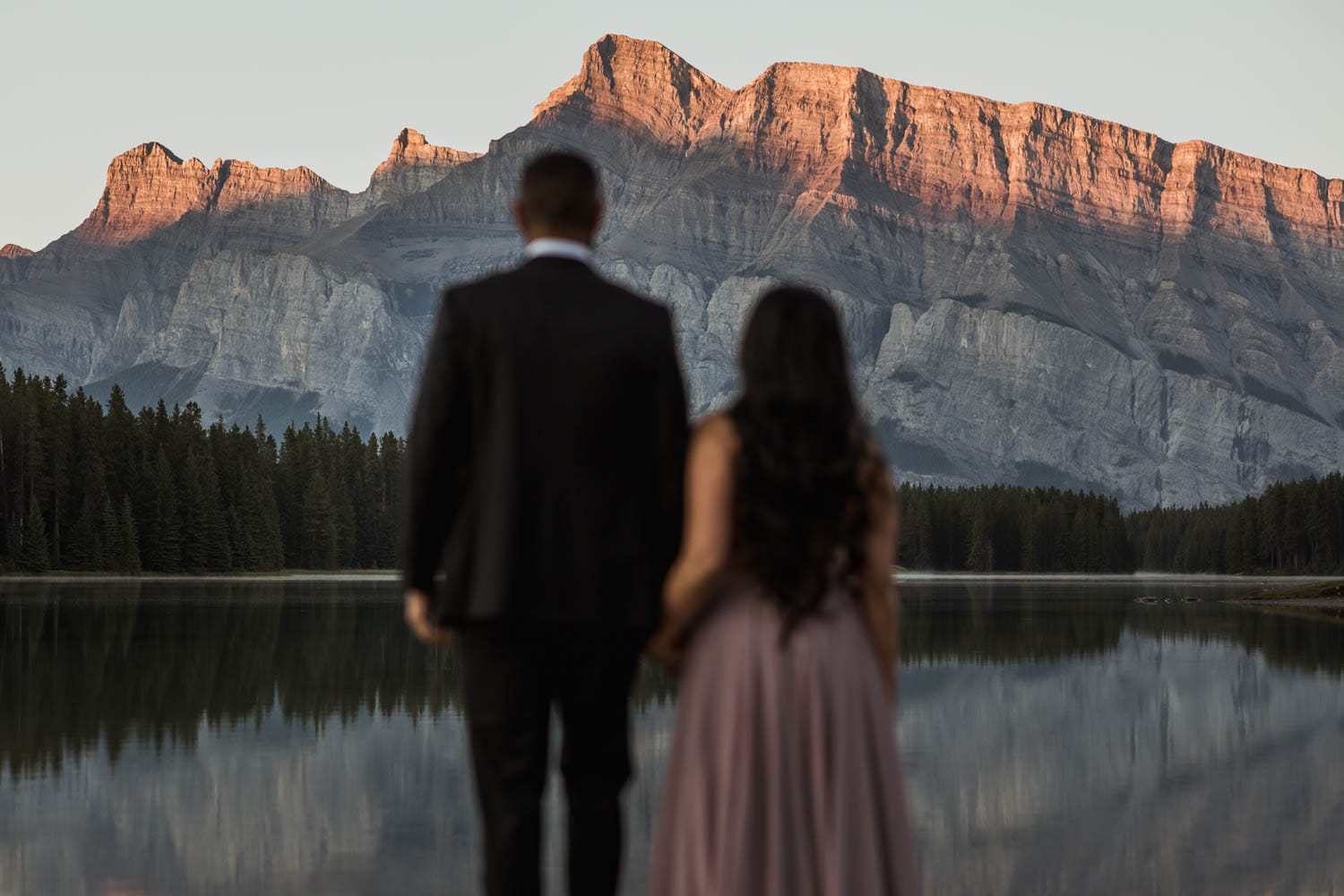 Engaged Couple looking at mountains in Banff
