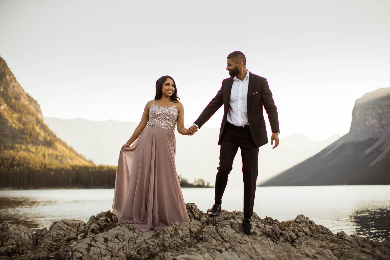 bride and groom holding hangs walking near lake minnewanka
