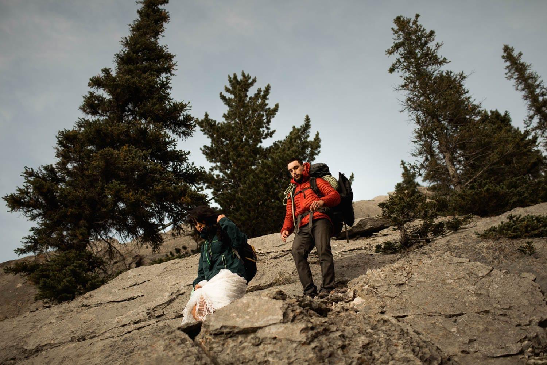 bride and groom climbing down mountain